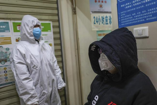 A medical worker in protective gear checks a patient suspected of being ill with coronavirus at a community health station in Wuhan